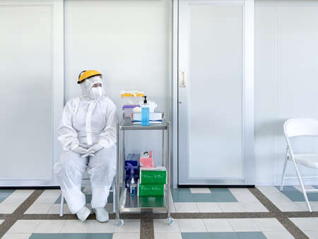 medical personnel wearing white PPE protective suit mask gloves sitting In front of the laboratory examine the infected patients