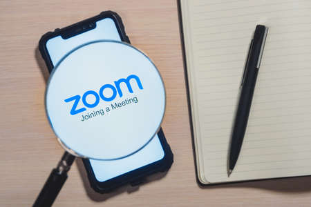Zoom app logo on the screen smartphone closeup. Zoom Video Communications is a company that provides remote conferencing services. Daily planner with a pen.