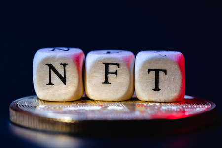 A NFT (non-fungible token) is a special crypto token that uses blockchain technology to link with a unique digital asset. The word NFT is laid out of cubes with letters on golden cryptocoin. Standard-Bild