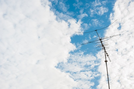 an antenna with blue sky and cloud