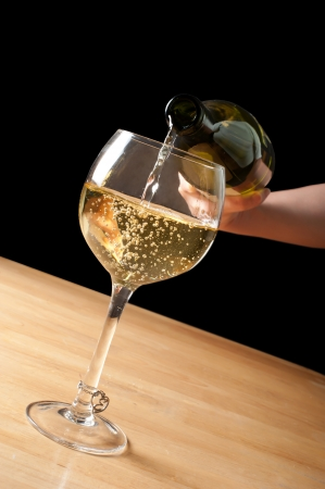 pouring white wine into a wineglass  photo
