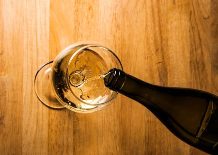 pouring white wine into a wineglass on table