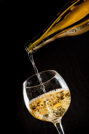 pour: pouring white wine into a wineglass on table