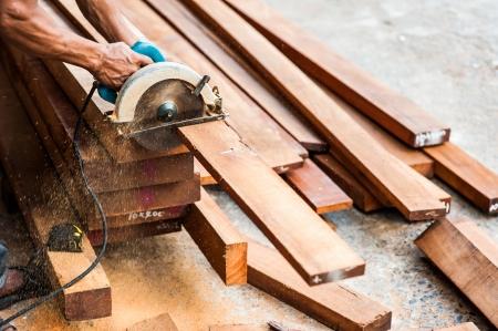 sawed: Wood being sawed be electric saw