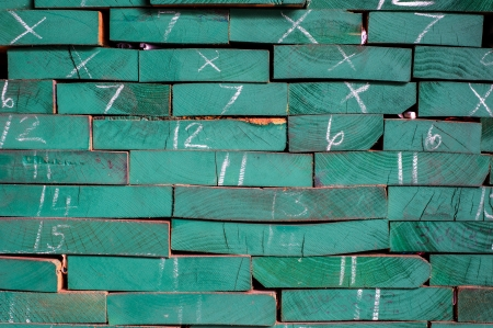 Pile of Wood Stored in stock painted green and marked size Stock Photo