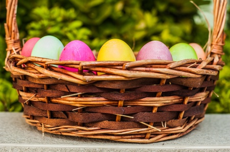 Colored eggs in basket with hay photo