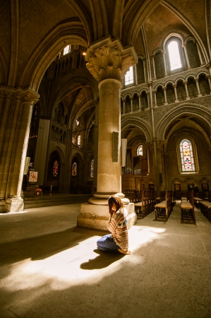 priesthood: Girl preying In side of Notre-Dame Cathedral - Lausanne, Switzerland Editorial