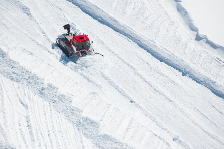 snowcat: A Tractor woking on snow field preparing for ski Stock Photo