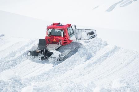 snowcat: A Tractor woking on snow field preparing for ski Editorial