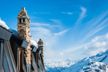 flue season: Chimney of Building on Snow Mountain Stock Photo