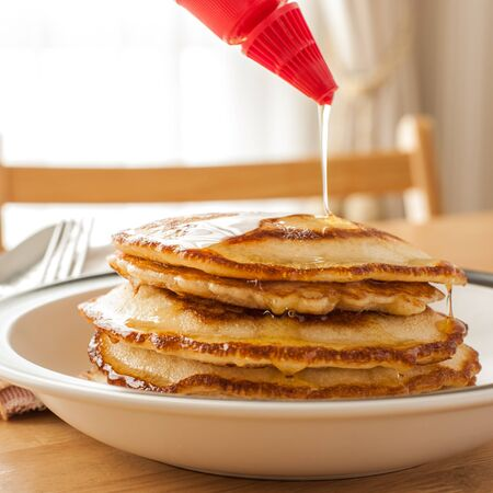 Pouring Honey onto Layers of pancake photo