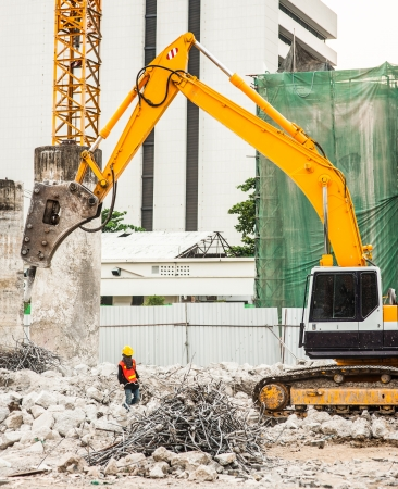 public works: Worker and Excavator in construction site Stock Photo