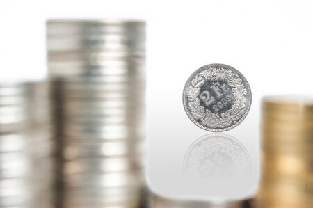 forground: Swiss Franc Coin with Blur Pile of Coin in forground