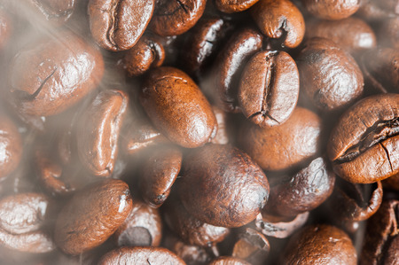Roasted Coffee bean with smoke on surface photo