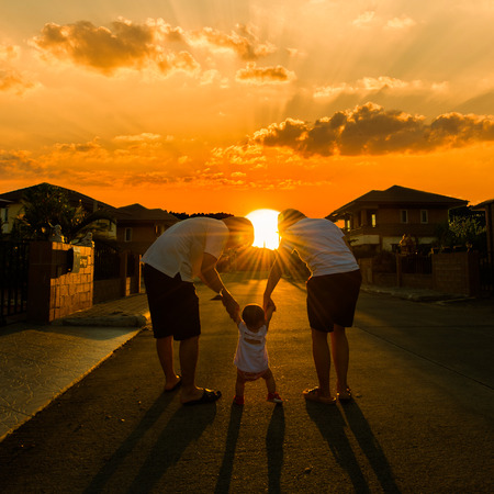 family escourting child to walk in sunset photo