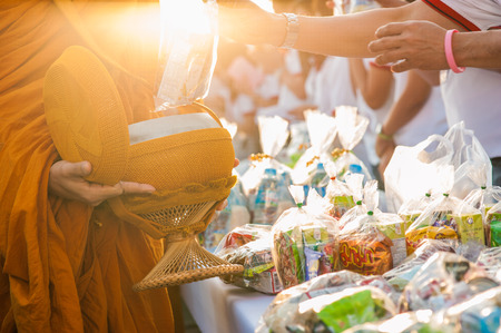 monks: Buddha Monk receiving food and items offering from people Editorial