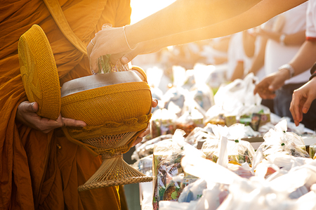 Buddha Monk receiving food and items offering from people Редакционное