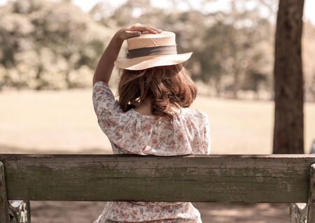 vintage girl holding hat for the wind blow