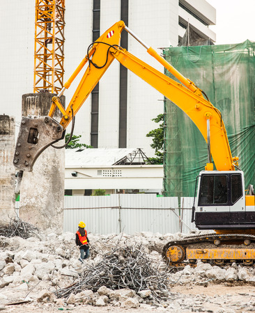 bagger: excavator and worker in construction site Stock Photo