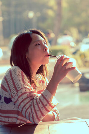 Young cute girl vintage style drinking water photo