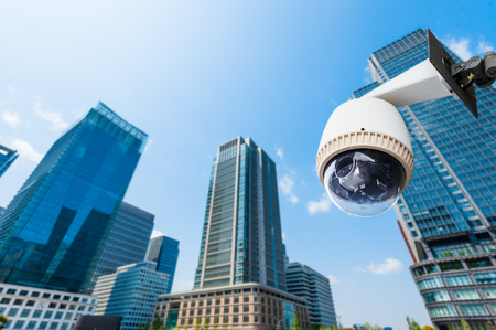 security monitoring: CCTV Camera or surveillance oeprating with building in background