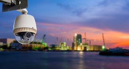 CCTV Camera or surveillance Operating with construction site near river in background photo