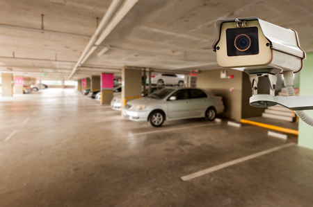 big brother spy: CCTV Camera Operating in car park building Stock Photo