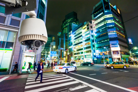 CCTV Camera or surveillance operating on street and building at night Stock Photo