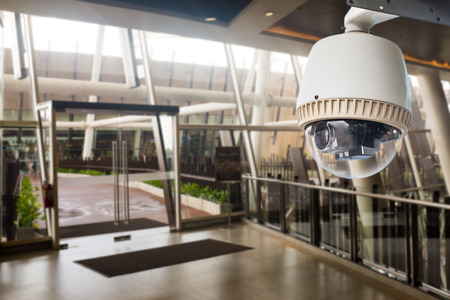 CCTV Camera operating in front of glass door Stock Photo
