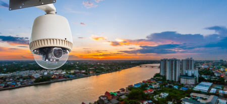 security guard man: CCTV Camera or surveilance Operating with city in background at sunset Stock Photo