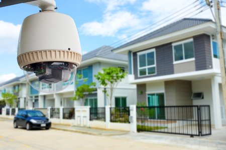 home security system: CCTV Camera or surveillance operating with village in background Stock Photo