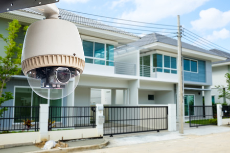 home security system: CCTV Camera or surveillance operating with house village in background Stock Photo