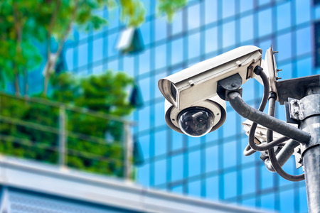 CCTV camera or surveillance operating in city with building in background photo