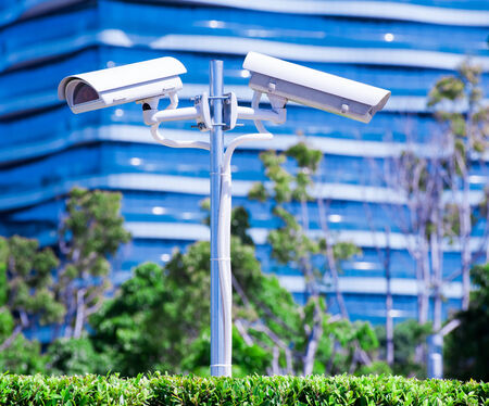 CCTV camera or surveillance operaiting with blue building and park in background photo