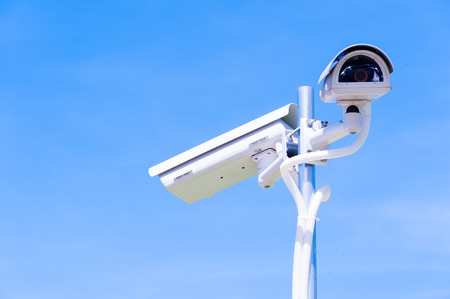 big brother spy: CCTV camera or surveillance operaiting on blue sky