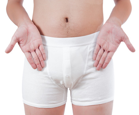 penis: close up of man on white boxer underware pointing at penis isolate on white background