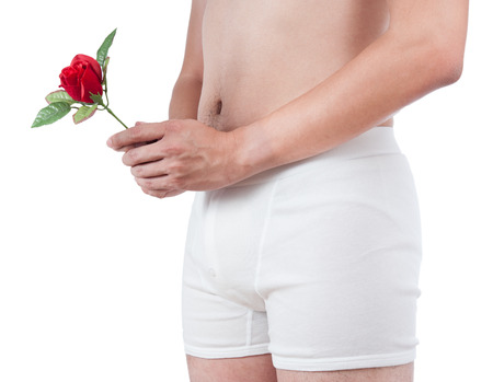 close up of man on white boxer underware  holding red rose isolate on white background photo
