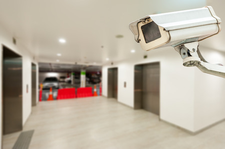 security guard man: CCTV operating in car park building with elevator Stock Photo