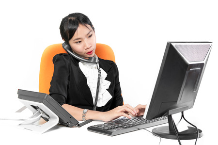 business woman phone: Young pretty business woman using phone with desktop computer Stock Photo