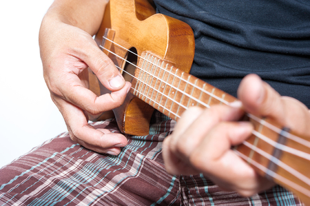 Hand playing ukulele, small string instrument Stock Photo