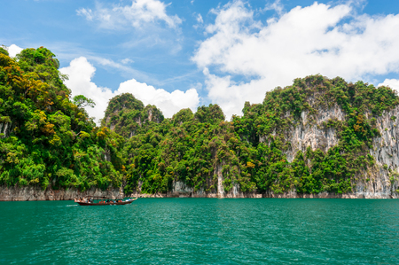 thai dam: Beautiful scene of boat on green clear water with rock mountain in Ratchaprapa Dam, Suratthani, Thailand Stock Photo