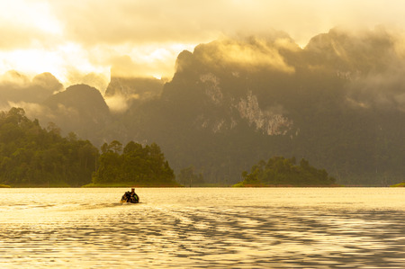 Beautiful scene of boat in morning at Ratchaprapa Dam, Suratthani, Thailand photo