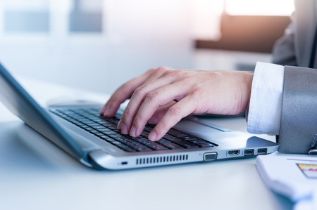 Close up of business man hands typing on laptop conputer photo