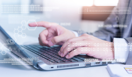 Close up of business man typing on laptop conputer with technology layer effect Stock Photo