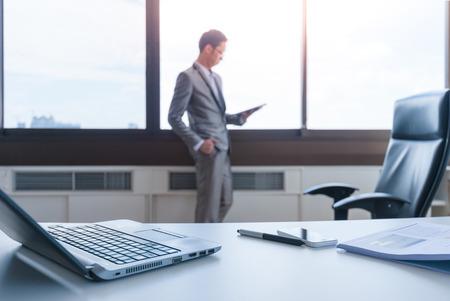 papeles oficina: desenfoque hombre de negocios de pie en la ventana que usa la tableta detr�s del escritorio de trabajo