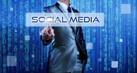 Business man with digital background pressing on button social media photo