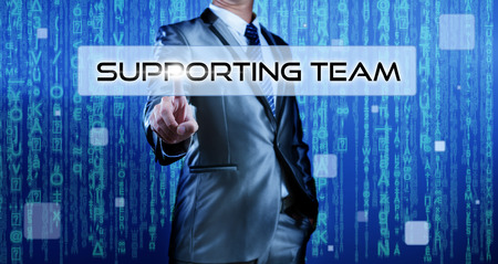 Business man with digital background pressing on button supporting team photo