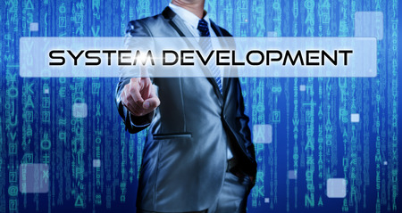 Business man with digital background pressing on button system development photo