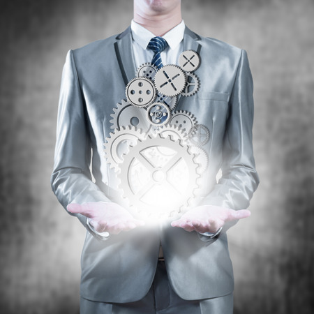 businessman holding gears in palms, business strategy concept photo