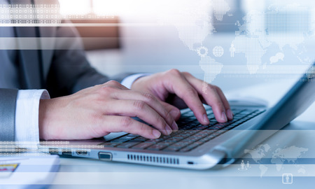 information international: Close up of business man typing on laptop conputer with technology layer effect Stock Photo